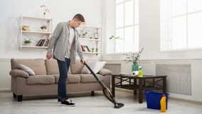 Young man cleaning house with vacuum cleaner. Young man cleaning house, washing floor with vacuum cleaner, copy space royalty free stock photos