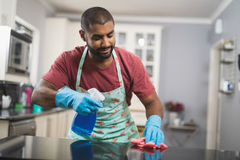 Young man cleaning marble counter in kitchen Stock Photo