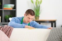 Young man cleaning sofa Stock Photos