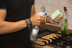 Young Man Cleaning Stove Top with Sponge Stock Images