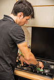 Young Man Cleaning Stove Top with Sponge Stock Photos