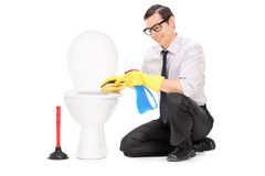 Young man cleaning a toilet bowl with a sponge Stock Images