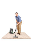 Young man cleaning with a vacuum cleaner Royalty Free Stock Image