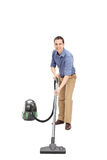 Young man cleaning with a vacuum cleaner Stock Image