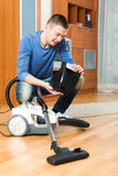 Young man cleaning vacuum cleaner Royalty Free Stock Photography