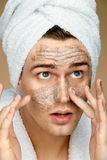 Young man cleans his face with scrub. Royalty Free Stock Image