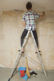 Young man cleans a wall from old wallpaper Royalty Free Stock Images