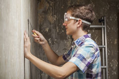 Young man cleans a wall from old wallpaper Royalty Free Stock Photo