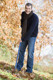 Young man clearing autumn leaves Stock Photos