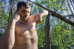 Young man with clenched fists on the backdrop of broken pines in the forest Stock Photos