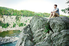 Young man on a cliff Stock Images