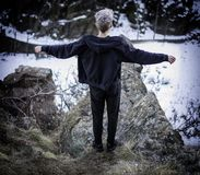 Young man on cliff edge. From above young man standing on edge of the cliff with hands apart in winter Stock Photo