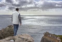 Young man on cliff`s edge Stock Photo