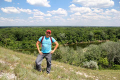 Young man climbed a hill over the river Stock Photo