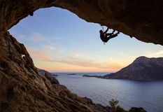 Young man climbing along ceiling of cave at sunset. Kalymnos island, Greece Royalty Free Stock Photography