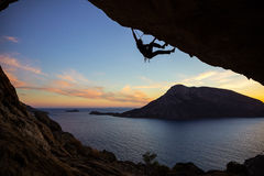 Young man climbing along ceiling of cave at sunset. Kalymnos island, Greece. Beautiful evening view of Telendos island in background Stock Photography