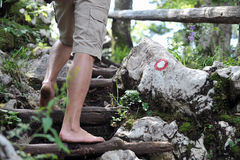 Young man climbing barefoot. Closeup with trail mark in the background Royalty Free Stock Images