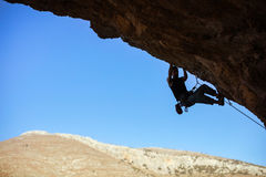 Young man climbing on ceiling of cave. Against blue sky Stock Photography