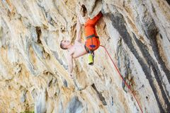 Young man climbing challenging route on overhanging cliff. Caucasian young man climbing challenging route on overhanging cliff royalty free stock photo