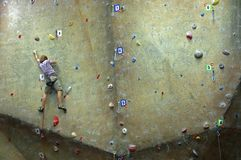 Young man climbing on a climbing wall. Royalty Free Stock Photography