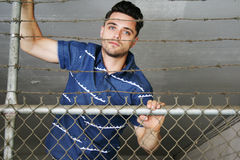 Young man climbing fence Stock Images