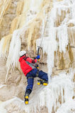 Young man climbing the ice. Using ice axe Royalty Free Stock Photo