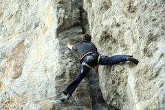 Young man climbing on a limestone wall with wide valley on the background Royalty Free Stock Photo