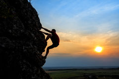 Young man climbing the mountain ridge. On sunset stock image