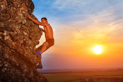 Young man climbing the mountain ridge. On sunset Royalty Free Stock Photography