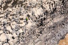 Young Courageous Man Climbing Natural Rock Wall Stock Images