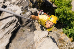 Young Man Climbing Rock. High angle portrait of young man climbing rock royalty free stock photos