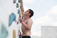Young Man Climbing A Rock Wall Royalty Free Stock Photos