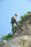 Young man climbing a rock wall Stock Image