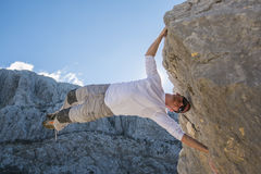 Young man climbing rock wall and hanging above gap Stock Images
