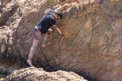 Young man climbing rocky wall without safety equipment royalty free stock photography