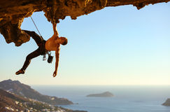 Young man climbing on roof of cave Stock Photography