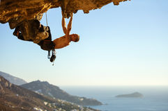 Young man climbing on roof in cave Stock Photos
