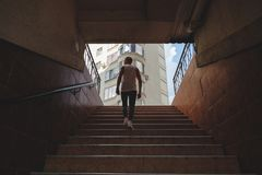 Young man climbing stairs in pedestrian subway stock photos