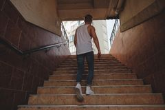 Young man climbing stairs in pedestrian subway. Going to the city. Fit boy rises from the urban underpass to a building royalty free stock photos