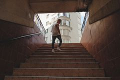 Young man climbing stairs in pedestrian subway royalty free stock photo