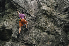 Young man climbing on stone rock Stock Photos