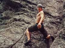 Young man climbing on stone rock, bouldering. Free climber young man climbing on stone rock outdoor in summer, bouldering. Space for text in right part of image Stock Photography