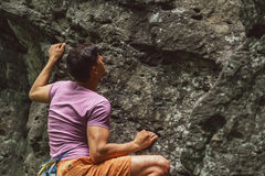 Young man climbing on stone rock. Outdoor in summer royalty free stock photo