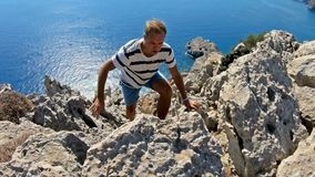 Young man climbing to the top of a high cliff. stock footage