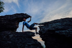 Young man climbing on top of rock  mountain Royalty Free Stock Image