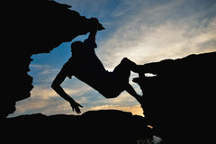 Young man climbing on top of rock mountain Stock Images