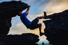 Young man climbing on top of rock mountain Royalty Free Stock Images