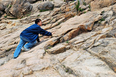 Young man climbing treacherous mountain cliff. Young man climbing treacherous steep mountain cliff full of rocks and boulders. Suitable for concepts such as Royalty Free Stock Photography
