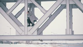Young man climbing under the bridge in cloudy day. Telephoto shot stock footage