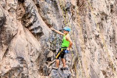 Young Man Climbing A Vertical Stone Wall Royalty Free Stock Images